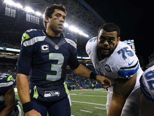 Seahawks quarterback Russell Wilson meets with Lions guard Larry Warford (75) following Seattle's 26-6 playoff victory Jan. 7, 2017.