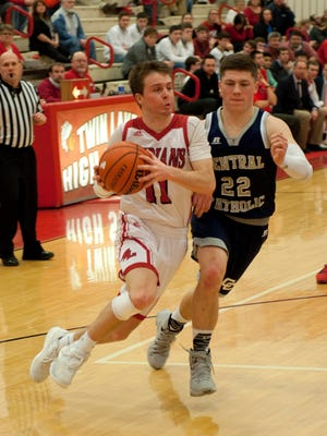 Twin Lakes' Justin Crabb drives.to the basket against Central Catholic's Jacob Page.