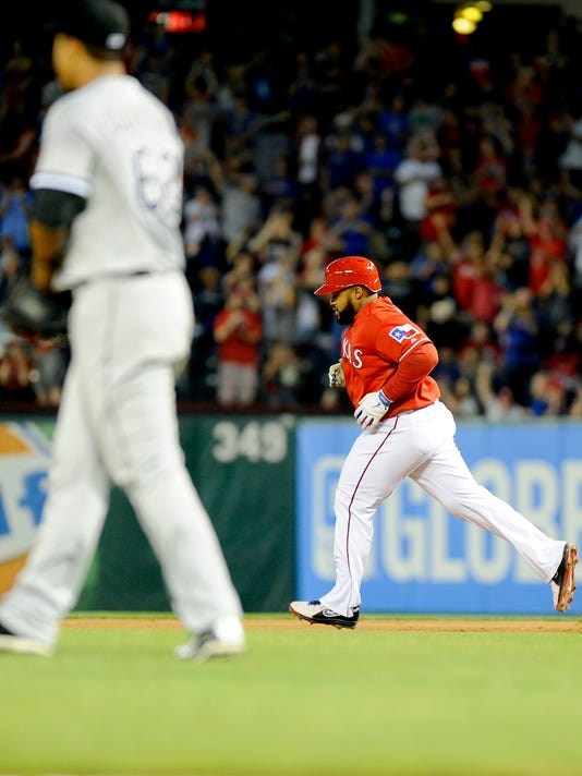 Chicago White Sox starting pitcher Jose Quintana, left, watches as Texas Rangers' Prince Fielder rounds the bases after a home run in the fourth inning of a baseball game on Saturday, April 19, 2014, in Arlington, Texas. (AP Photo/Matt Strasen)