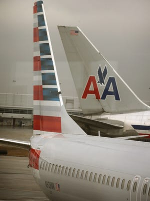 An American Airlines 737-800 aircraft (L) featuring a new paint job sits at a gate at Chicago O'Hare Airport as an aircraft with the old tail design passes by last January. Employees just voted to keep the new design, on the left.
