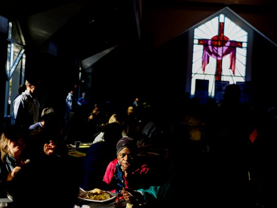 People enjoy a meal during the 31st annual Thanksgiving Day Celebration dinner for the needy served at KARM on Broadway in Knoxville, Tennessee on Thursday, November 23, 2017.