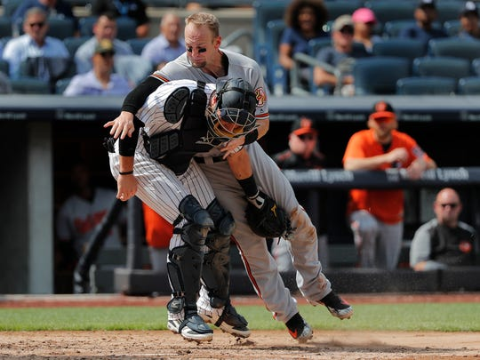 Baltimore Orioles' Caleb Joseph, right, is tagged out at the plate by New York Yankees catcher Austin Romine while attempting to score on a double by Renato Nunez during the fifth inning of a baseball game, Wednesday, Aug. 1, 2018, in New York.
