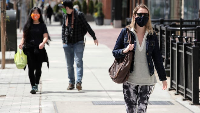 FILE - Pedestrians, wearing masks due to the coronavirus outbreak, walk down Boylston Street in Boston, Wednesday, April 15, 2020.