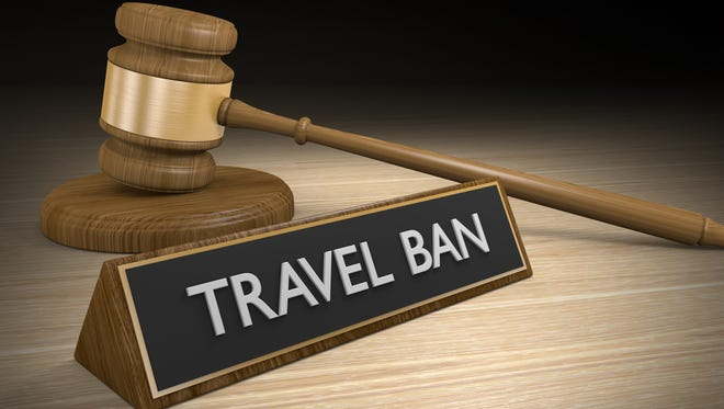 3D render of a wooden court gavel resting next to a sign that says travel ban.
