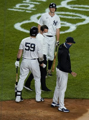 A trainer checks on New York Yankees' DJ LeMahieu in a recent game.