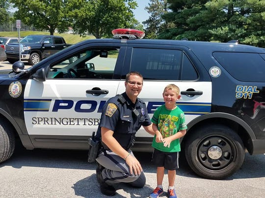 6-year-old Lucas Buckler poses with Officer Cory Landis in front of his police vehicle Saturday afternoon at Springettsbury Township Park.