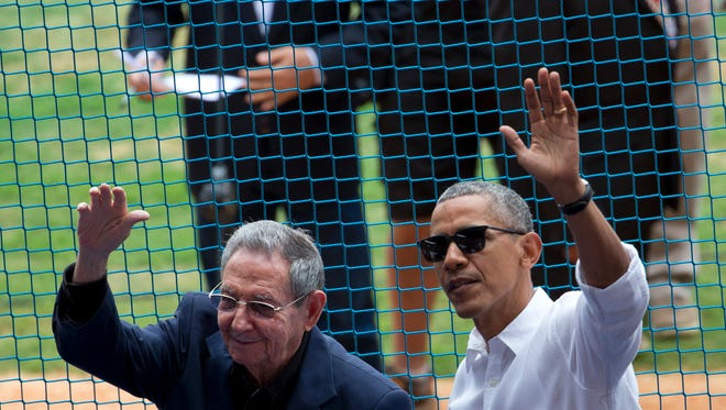 U.S. President Barack Obama (right) and his Cuban counterpart, Raul Castro, wave to cheering fans as they arrive for a baseball game between the Tampa Bay Rays and the Cuban national baseball team in Havana, Cuba, on May 22, 2016.