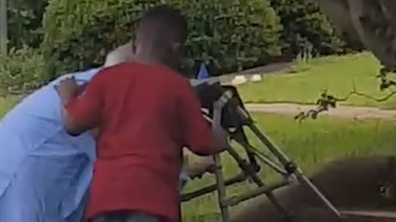 Boy jumps out of SUV to help woman struggling with walker