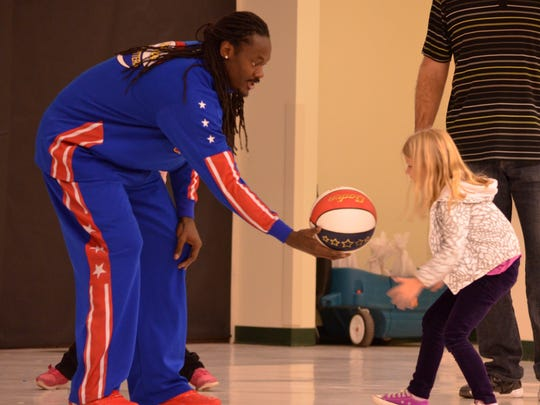 """Second grader Ella Jones reaches takes the basketball as she participates in a version of the Harlem Globetrotters famous """"Magic Circle."""""""