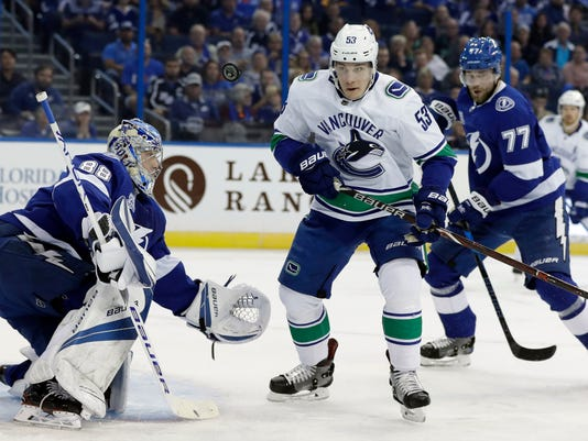 Vancouver Canucks center Bo Horvat (53) goes after the puck after blocking a shot in front of Tampa Bay Lightning goaltender Andrei Vasilevskiy (88) and defenseman Victor Hedman (77) during the first period of an NHL hockey game Thursday, Feb. 8, 2018, in Tampa, Fla. (AP Photo/Chris O'Meara)