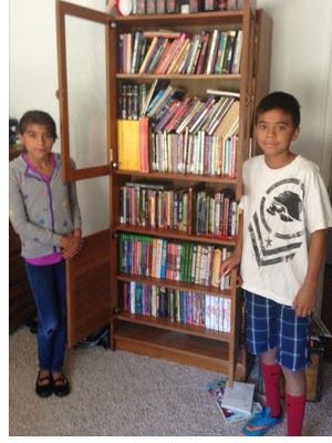 Mathew Flores, 12, stands with a bookshelf full of donated books.