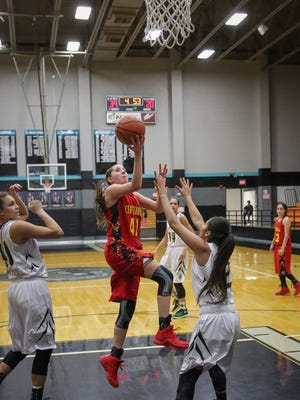 Centennial's  Kaela Chavez drives to the basket when being guarded by Mayfield's Mikayla Sago Tuesday night during a Holiday Hoopla Tournament first round game at Oñate High School.