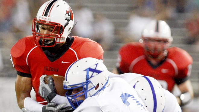 Colerain's Damon Sims tries to break free from a tackle by St. Xavier's Luke Kuechly during the first half in the second game of the Skyline Chili Crosstown Showdown on Friday August 22, 2008.