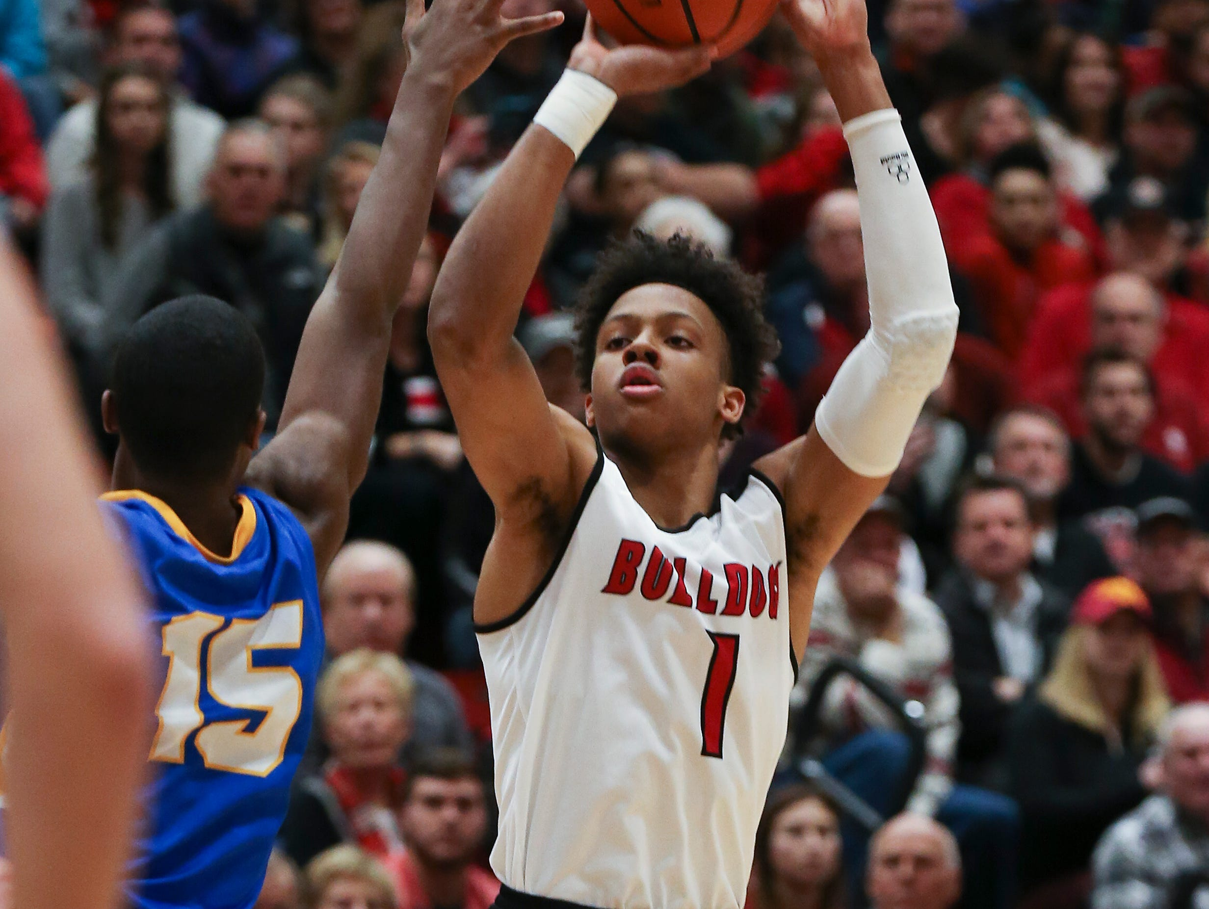 New Albany's Romeo Langford (1) shoots against Carmel's Jalen Whack (15) during their game at New Albany High School. New Albany edged Carmel 55-52. Dec. 20, 2016