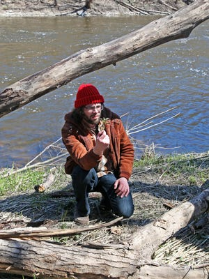 Kyle Denton holds a nettle while leading an herb walk along the Milwaukee River in Riverwest on April 29, 2018.
