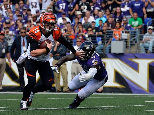 Cincinnati Bengals quarterback Andy Dalton (14) stiff-arms Baltimore Ravens inside linebacker C.J. Mosley (57) as he runs during the first quarter at M&T Bank Stadium.