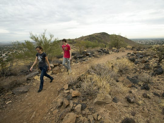 Amy Hoeptner of Tolleson and Eric Bradley of Phoenix hike on the Cholla Loop Trail in the Glendale Thunderbird Conservation Park on November 17, 2017.