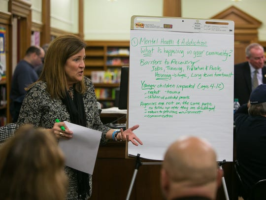 Becky King leads a group discussion about mental health and addiction at a community forum organized by the Behavioral Health Consortium at P.S. du Pont Middle School in Wilmington on Tuesday night.