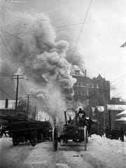 In this view along Gilmore Street, looking toward Hudson Avenue, smoke billows from the American Brewing Co. Two fire engines parked side-by-side occupy the entire width of Gilmore Street. The fire occurred on Jan. 19, 1920.