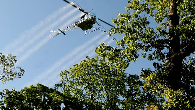 Hanover Twp--May 21, 2009--A helicopter flies over Hanover as the township sprays to kill gypsy moths caterpillars whose primary diet consists of  oak trees found in the area.