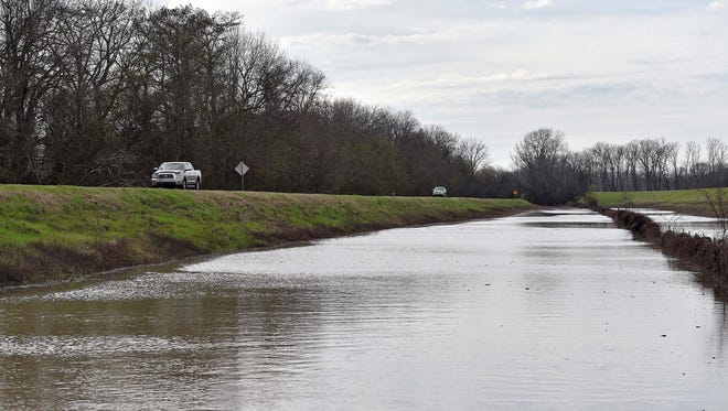 In this Dec. 31, 2015, photo, motorists drive down Mississippi 465 as floodwater slowly encroaches on the road that passes through Warren and Issaquena counties on its way to Eagle Lake north of Vicksburg, Miss.