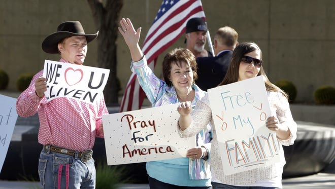 Carol Bundy, wife of Nevada rancher Cliven Bundy, center, her son Arden, left, and her daughter Stetsy Cox, protest outside Lloyd George Federal Building on Thursday, March 17, 2016, in Las Vegas. Nevada rancher Cliven Bundy lost a renewed bid Thursday for release from jail ahead of trial on federal conspiracy and assault charges stemming from an armed standoff against government agents two years ago.  (Bizuayehu Tesfaye/Las Vegas Review-Journal via AP) LOCAL TELEVISION OUT; LOCAL INTERNET OUT; LAS VEGAS SUN OUT