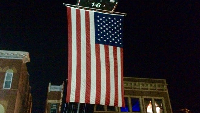 A firetruck from Salisbury Station 16 hangs a large American flag as a backdrop to the downtown medal ceremonies.