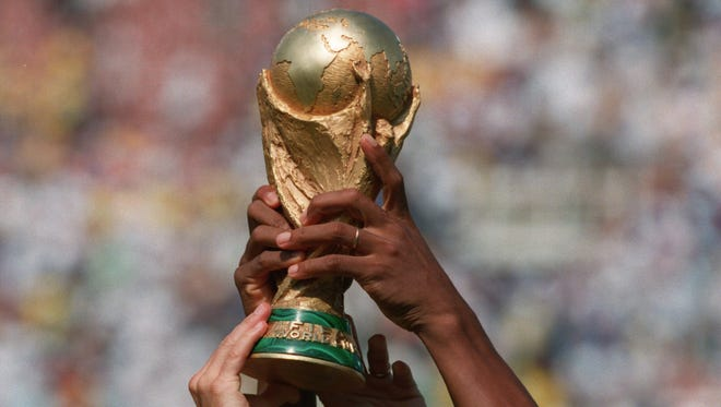 Brazilian hands lift the World Cup after the match.