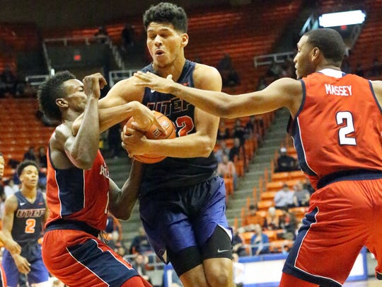 UTEP forward Paul Thomas holds on to the ball while driving to the basket against Florida Atlantic's Marcus Neely, left, and Justin Massey, 2, Saturday night. The Miners pulled away for another victory with a 66-65 win in overtime.