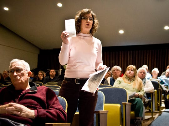 Carrie Neuschel, who questions the benefits of a 1 percent Colchester local option tax, holds up literature by the Colchester Community Development Corporation in support of the tax. Residents debated the proposed tax at length Monday night at Colchester High School in advance of a Tuesday vote.