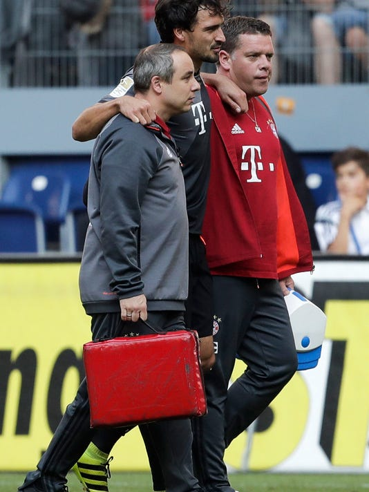 Bayern's Mats Hummels, center, is helped by medical staff to leave the pitch after being injured during the German Bundesliga soccer match between Hamburger SV and FC Bayern Munich in Hamburg, Germany, Saturday, Sept. 24, 2016. (AP Photo/Markus Schreiber)