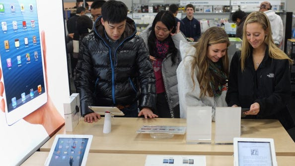 Shoppers gather around a display for the Apple ipad mini inside of a Best Buy store in Rockville, Md., during a Black Friday sale in 2012.