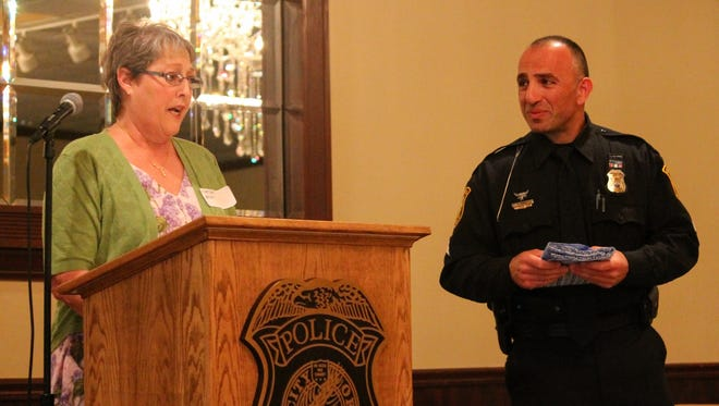 Livonia resident Martha Breen presents Sgt. Ron Warra with a gift as thanks for his work with the previous citizens police academy at the banquet held in May. A second citizens police academy will take place starting in February.