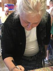 Longtime Joe's customer Margaret Castillo signs a good