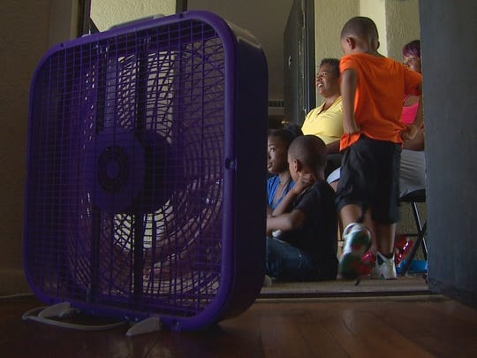 Residents use a box fan to keep cool