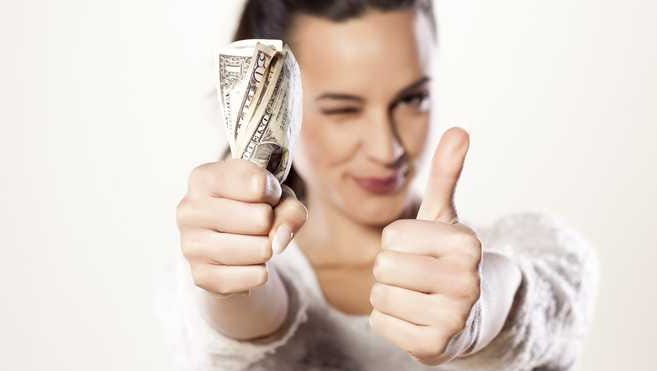 Woman giving thumbs up with other hand full of money.