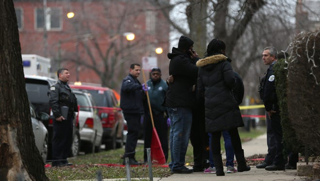 Chicago police officers talk with relatives of one of the two people killed by a police officer in the entry of a Chicago apartment Saturday.