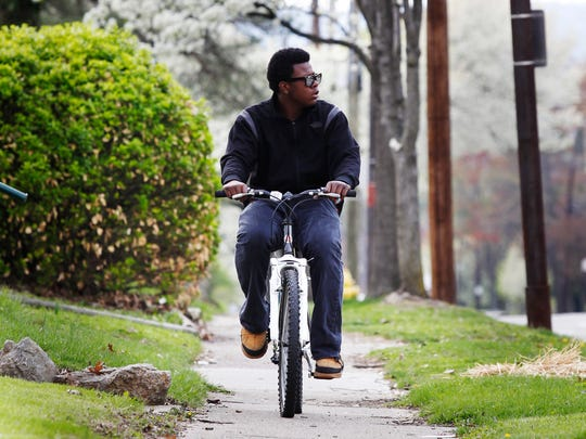 Malik Nu'qman of Avondale rides his bike along Mitchell Avenue after school.