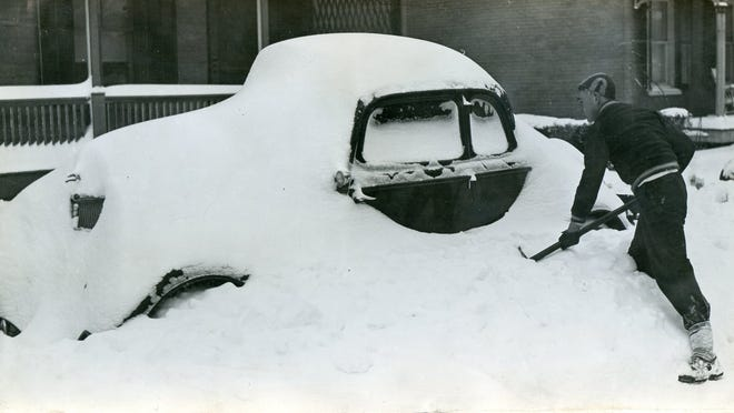 A City of Poughkeepsie resident tries to dig out a car for a neighbor on Garden Street near Mansion Street in November 1938.