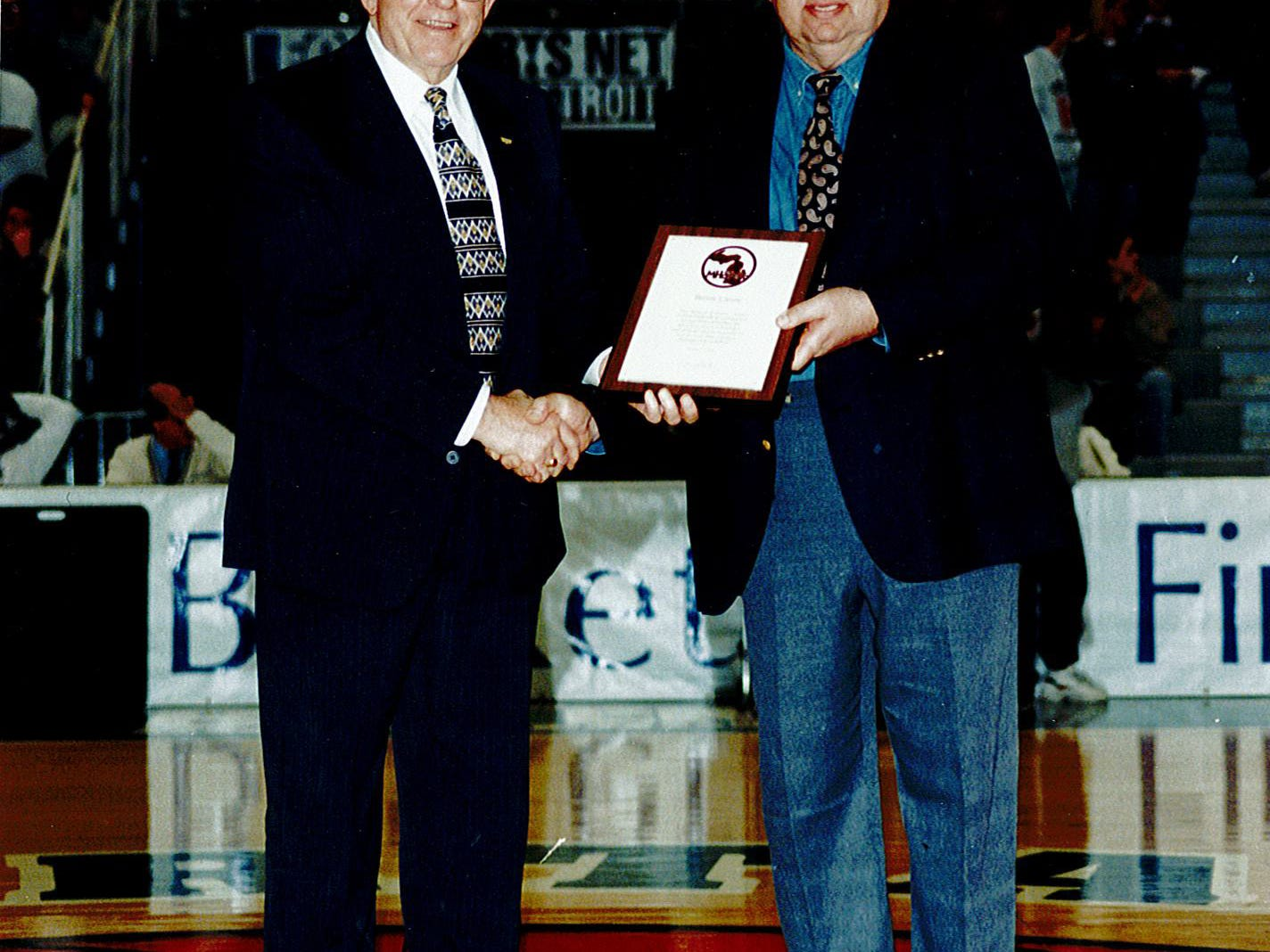 Bernie Larson (right), here receiving the MHSAA Forsythe Award in 1999, returned home Wednesday following a six-week hospital stay.