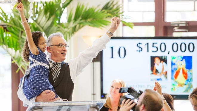 Cancer survivor Avery McCaskill, 6, and auctioneer Scott Robertson celebrate during the Southwest Florida Wine & Food Fest auction on Saturday at the Miromar Lakes Beach and Golf Club.