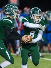 St. Johnsbury's Jacob Cady, left, fakes a hand off