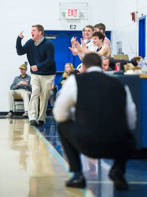 Mt. Mansfield Union coach Jeff Davis, left, and his bench cheer as Rice Memorial coach Paul Pecor, right, ponders his next move in Jericho on Tuesday, January 30, 2018.