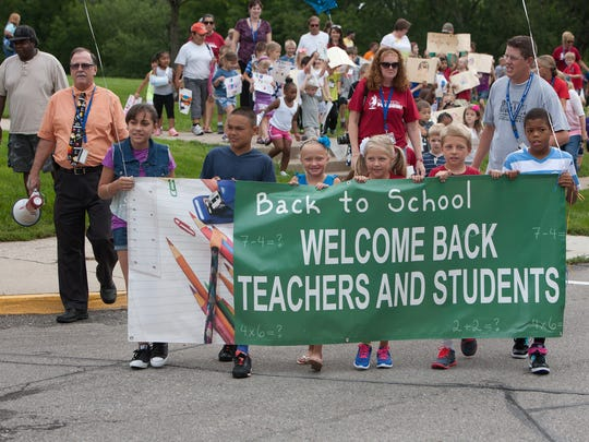 """Perkins Elementary School students and staff head on on their annual """"Back to School"""" parade around the neighborhood on Friday morning, August 22, 2014."""