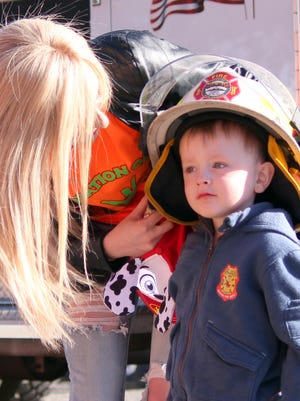 """""""Cancer Warrior"""" Eli Goedecke made a grand entrance to the 11th annual Celebration of Life Cancer Walk on Saturday at Voiers Park. Eli asked the fire department for a ride to the park on a real fire engine. Goedecke had his fire helmet adjusted by his big sister Chloe."""