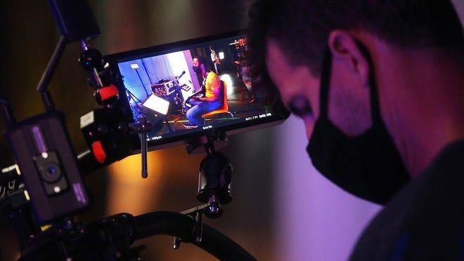 Cameraman Brent Veverka records a Facebook livestream of DTC Organ Trio at AVclub in Akron.