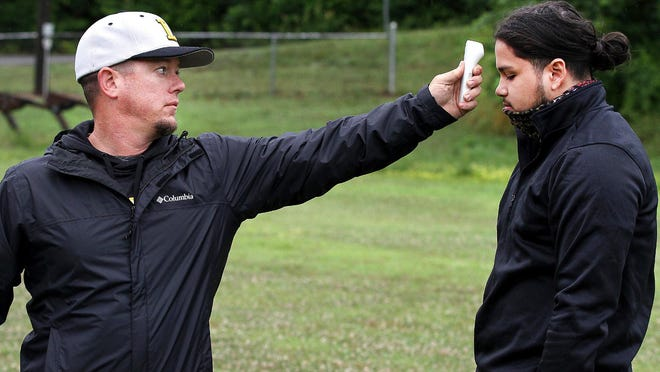 Assistant coach Brent Gates takes Diego Ramiro's temperature as part of COVID-19 protocol before Lincolnton High School's football practice Wednesday morning.