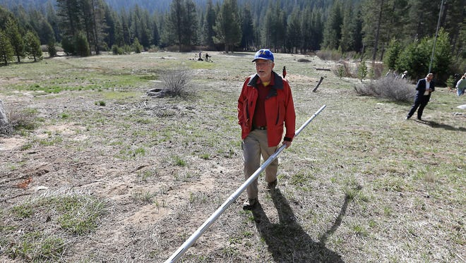 Frank Gehrke, chief of the California Cooperative Snow Surveys Program for the Department of Water Resource, carries a snow pack measuring tube as he does a preliminary walk around the meadow where the snow survey is held near Echo Summit, Calif., Wednesday, April 1, 2015. Gehrke said this was the first time since he has been conducting the survey at that he found no snow at this location at this time of the year.