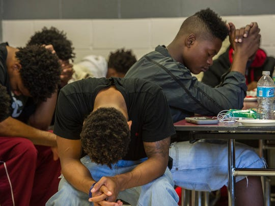 Maplewood football players pray after hearing an inspirational