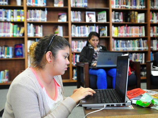 Rosa Valle, 18, works on a computer in Linda Wyncoop's